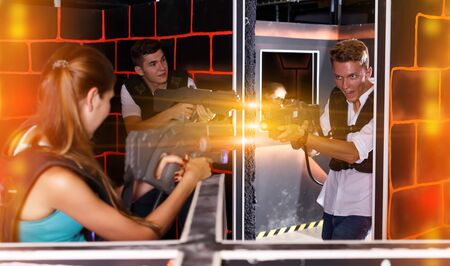 team of players with plastic laser pistols in their hands playing laser tag
