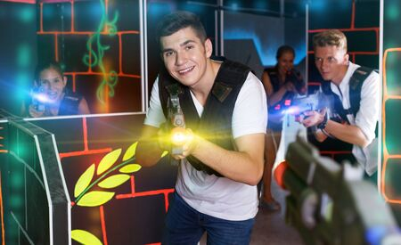 Group of young smiling people in vests and with laser pistols playing emotionally laser tag game in  room