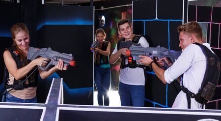 Two exciting players man and woman standing opposite each other with laser weapons in dark laser tag room