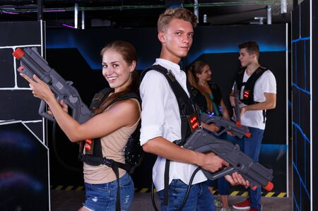 Excited team of laser tag guy and girl with  laser pistols  and friends in background
