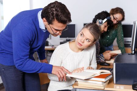 Male teacher helping female student preparing for exam in computer class of university library Stock Photo