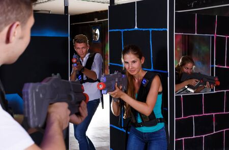 Two exciting players guy and girl standing opposite each other with laser guns in dark laser tag room