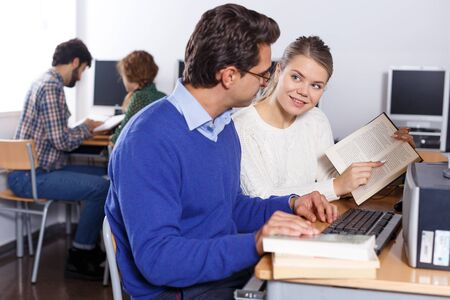 Couple of adult students reading textbook together while studying in university computer class