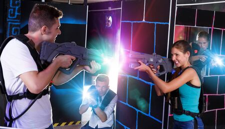 Two laser tag teams standing opposite each other with laser pistols in dark room