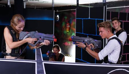 Two exciting players guy and girl standing opposite each other with laser weapons in dark laser tag room