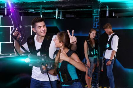 Triumphing team of laser tag winners guy and girl in foreground and losers team in background