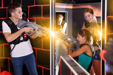 Cheery  players young mens and womens playing in teams in dark laser tag station Imagens