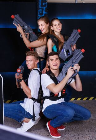 Group portrait of joyful cheerful positive smiling people with laser guns in their hands in room for playing laser tag