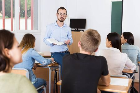 glad young teacher is giving lecture for students with book in the class. Stock Photo