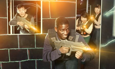 Emotional African man with the laser pistol playing laser tag with friends at dark labyrinth Foto de archivo