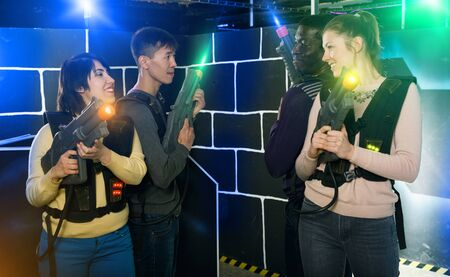 Two happy  young girls standing face to face with laser guns on lasertag gaming arena Stok Fotoğraf