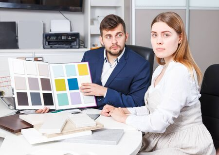Positive girl consulting with salesman in furniture salon