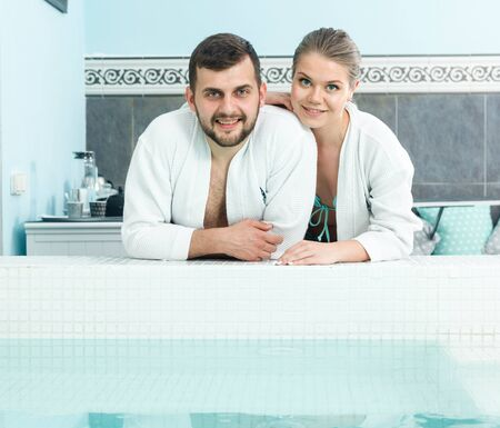 Portrait of young happy couple in bathrobes near pool during wellness weekend in spa salon
