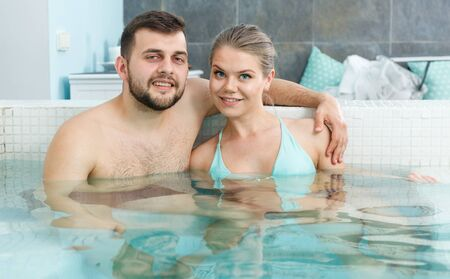 Happy young couple relaxing in jacuzzi in thermal spa