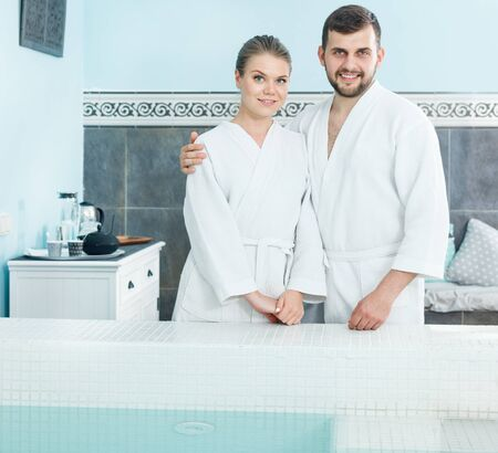 Cheerful young couple in bathrobes standing next to pool in a spa center. Focus on both persons Stok Fotoğraf
