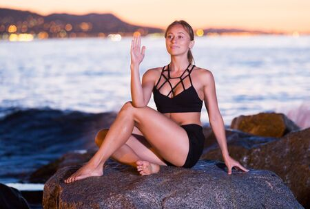 Glad young woman is practicing stretching on a rock near sea at the dawn.