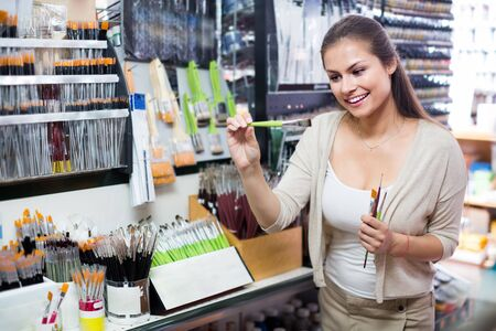 Young hilarious woman shopping various paintbrushes in art store Banco de Imagens