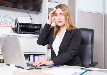 Disappointed young business woman working on laptop in salon 写真素材 - 129694632