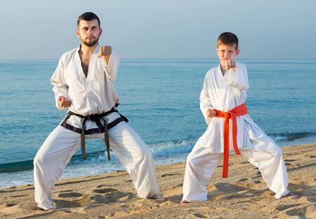 Smiling man and little boy exercising karate in morning outdoor Фото со стока