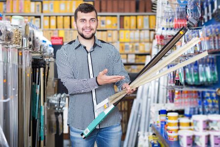 Smiling man choosing new molding in houseware store Banco de Imagens