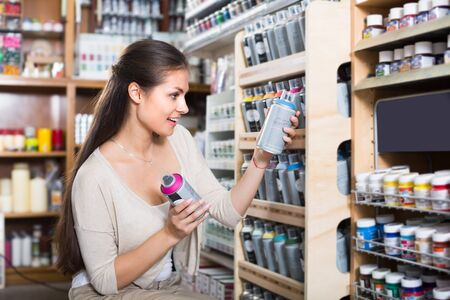 Young smiling woman shopping acrylic color spray can in art store