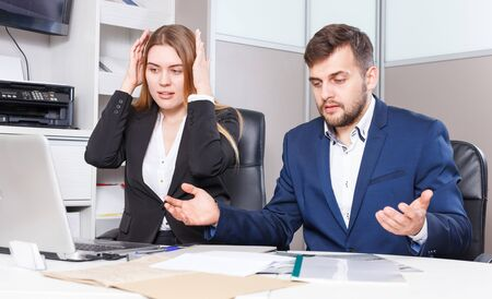 Frustrated female and male sales managers working in showroom, looking at laptop monitor