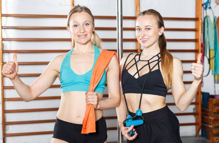 Portrait of two happy fit young women in modern fitness gym