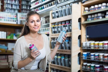 caucasian woman shopping acrylic color spray can in art store 写真素材