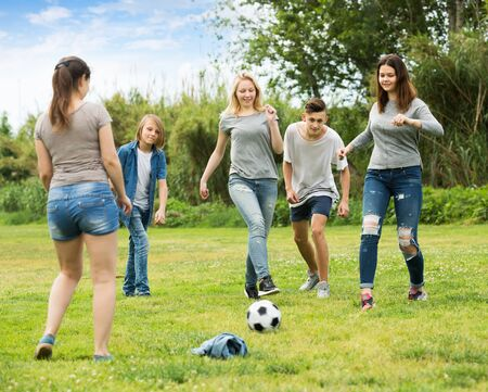 Three positive girls and two boys teenagers friends running with ball on meadow outdoors Фото со стока