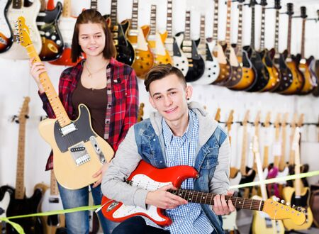 Teenage boy and girl choosing best electric guitar at guitar shop. Focus on boy Stock Photo - 129664760