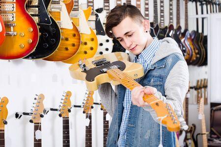 Smiling european teenage customer deciding on suitable amp in guitar shop Stock Photo - 129664247