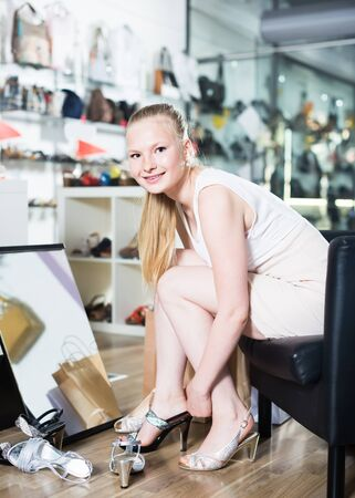 Young woman of model appearance is trying on heeled sandals in boutique