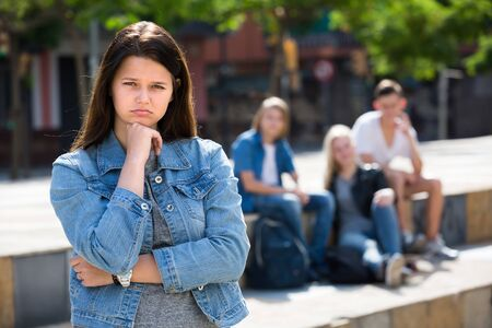 lonely teenage girl standing away from friends feeling depressed