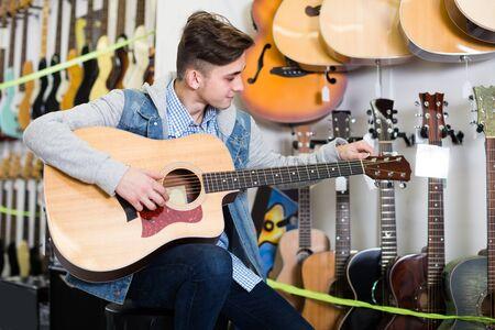 Teenager is choosing quality acoustic guitar in guitar shop.