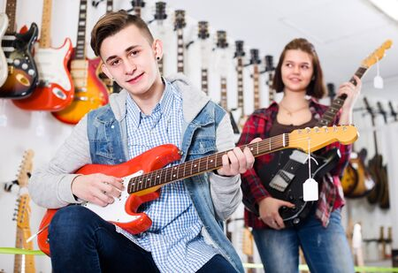 Female and male rock-n-roll players are deciding on suitable amp in guitar shop. Stock Photo