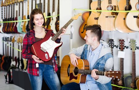 positive european teenage customers comparing amp and acoustic guitar in guitar shop Stock Photo - 129664025