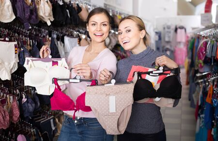 two happy european female customers holding bras and panties in hands in underwear store