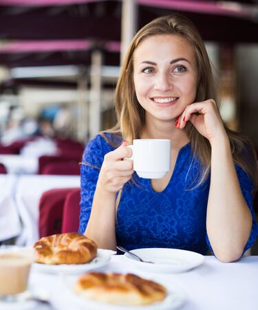 Girl is drinking coffee with croissant in time breakfast in cafe.