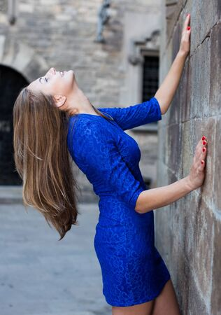 Young woman is posing in blue dress near old wall in city. Stockfoto