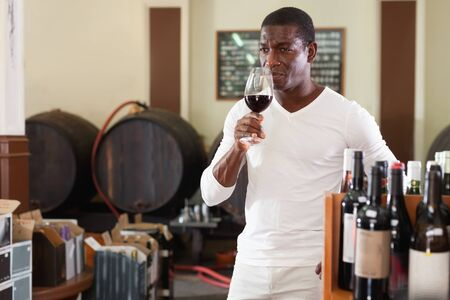 Confident happy cheerful  african american male winemaker inspecting quality of red wine, checking it in wine store