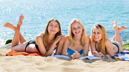 Portrait of three happy young women wearing swimsuits having fun together on beach Stockfoto