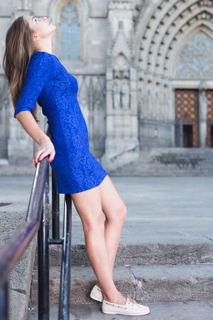 Elegant girl is posing in blue dress on the street of old city. Stockfoto