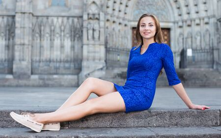 Cheerful female is playfully posing sitting in blue dress on the stairs outdoor. Stockfoto