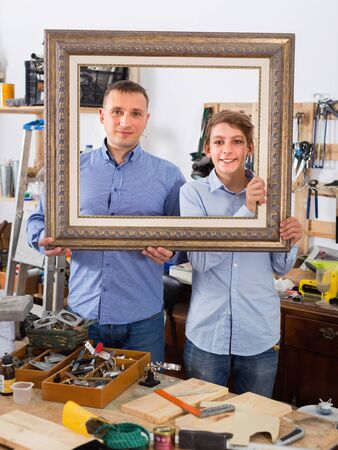 Portrait of happy adult  man and boy  displaying  frame in interior studio