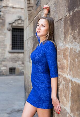 Cheerful female is playfully posing in blue dress near wall of building outdoor.