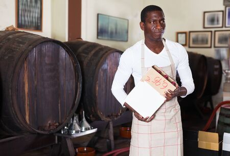 Positive diligent cheerful afro seller working in wine store, holding box full of bottles with wine