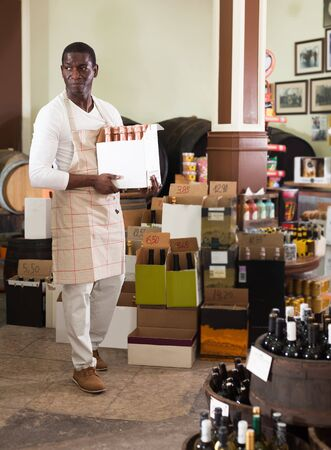 Confident African American vendor holding a cardboard box with bottles of wine in a liquor store