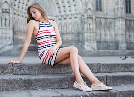 Elegant girl is sitting on the stairs and posing outdoor. Stockfoto