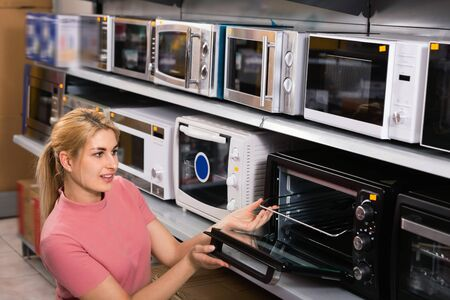 Young glad cheerful positive housewife  choosing new modern mini oven for kitchen in furniture shop