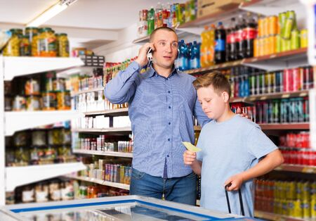 glad adult man talking on phone while visiting supermarket with preteen son 스톡 콘텐츠